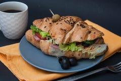Frühstücksnahrung mit Kaffee Hörnchen-Sandwich mit Fried Eggs und Frischgemüse auf Gray Plate mit orange Serviette über dunklem G Stockbild