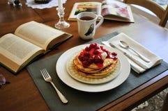 Frühstückspfannkuchen mit der Kirsche, die auf dem Tisch übersteigt Stockbild