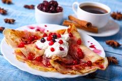Frühstückspfannkuchen mit Kirschmarmelade auf blauem Hintergrund Stockfotos