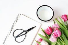 Frühstücksszene mit Becher von Milch, von schwarzen Scheren der Weinlese, von leerem Notizbuch und von Blumenstrauß der rosa Tulp Lizenzfreie Stockbilder
