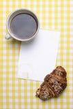 Frühstücksszene mit Kaffee, Hörnchen, Stau und leerem Papier Stockbilder