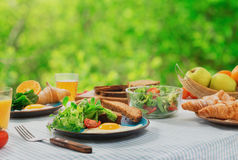 Frühstückstisch mit gesunder Nahrung Spiegeleier, Salat, Hörnchen stockfotografie