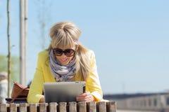 för dator tablet utomhus genom att använda kvinnan Fotografering för Bildbyråer