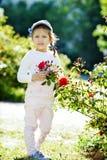 För flicka rosa buske nära Royaltyfri Foto