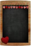 För ginghamförälskelse för svart tavla som röda valentin hjärtor hänger på trä Fotografering för Bildbyråer