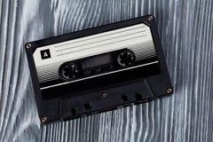 för gitarrillustration för begrepp elektrisk musik Svart ljudkassett på den gråa träbakgrunden Tappning retro stil slapp fokus Arkivfoton