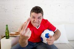 För innehavboll för ung man lek för fotboll hållande ögonen på på tv som gör en gest upprivet och galet ilsket ge fingret Fotografering för Bildbyråer