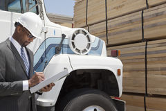För leverantörhandstil för afrikansk amerikan manliga anmärkningar, medan stå, genom att logga lastbilen Arkivbilder