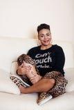 För mammakvinnan för den nätta stilfulla afrikanska amerikanen klädde den stora brunnen byltet kopplar av hemma, leopardtrycket p Arkivfoton