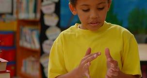 Fr?mre sikt av afrikansk amerikanskolpojken som r?knar med hans finger p? skrivbordet i ett klassrum p? skola 4 arkivfilmer