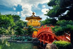 Fr?mre sikt den guld- paviljongtemplet med den r?da bron i den Nan Lian tr?dg?rden, Hong Kong askfat royaltyfria foton
