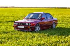 Fr?mre v?nster sida av en gammal tysk bil som st?r p? gr?nt gr?s p? solnedg?ngen royaltyfri fotografi