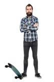 För plädtartan för säker skäggig hipster som bärande skjorta poserar med hans skateboard Arkivfoton