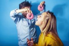 Fr?re heureux et soeur de famille mangeant des but?es toriques sur le fond bleu, consommation de concept de personnes de mode de  photos stock