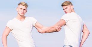 Fr?res de jumeaux musculaires d'hommes ? l'arri?re-plan blanc de ciel de chemises concept de confr?rie Avantages de avoir le fr?r photographie stock libre de droits