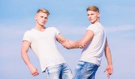 Fr?res de jumeaux musculaires d'hommes ? l'arri?re-plan blanc de ciel de chemises concept de confr?rie Avantages et inconv?nients photo libre de droits