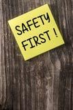 För säkerhet gul klibbig anmärkningsstolpe först det Arkivfoto