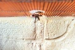För skumbeläggning för termisk isolering rör och elkraftlinjer på konstruktionsplatsen för nytt hus Royaltyfria Bilder
