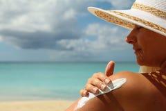 För solskydd för flicka aplying kräm Arkivfoton