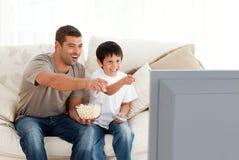 för sontelevision för fader lyckligt hålla ögonen på Arkivbild
