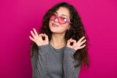 För ståendeshowen för den unga kvinnan som formar det härliga tecknet för godkännandet poserar på rosa bakgrund, långt lockigt hå Fotografering för Bildbyråer