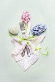 För tabellställe för påsk festlig inställning med blommor, dekorägget och bestick på ljus bakgrund Arkivbild