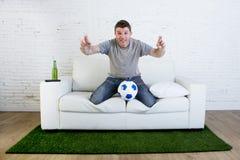 För tvfotbollsmatch för fotbollsfan hållande ögonen på spänning nervöst c för lidande Arkivbild
