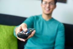 För TVändringar för asiatisk man hållande ögonen på kanal med fjärrkontrollen Arkivfoton