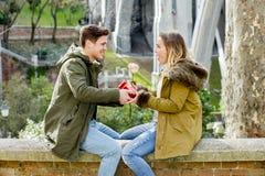 För valentindag för unga härliga par steg förälskade fira gåvor och Arkivfoton