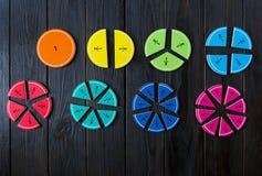 Frações coloridas da matemática no fundo ou na tabela de madeira marrom matemática interessante para crianças Educação, de volta  imagens de stock royalty free