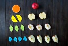 Frações e maçãs coloridas da matemática como uma amostra no fundo ou na tabela de madeira marrom matemática interessante para cri imagem de stock