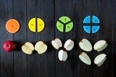 Frações e maçãs coloridas da matemática como uma amostra no fundo ou na tabela de madeira marrom matemática interessante para cri fotografia de stock
