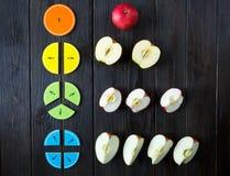 Frações e maçãs coloridas da matemática como uma amostra no fundo ou na tabela de madeira marrom matemática interessante para cri foto de stock royalty free