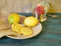 A fraîchement coupé en tranches le citron sur un plateau, table en bois, pommes, bonbons, composition saisonnière, vue supérieure photos stock