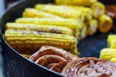 Fraîchement cuit sur le maïs de jaune de gril avec des anneaux de saus frit image stock
