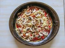 A fraîchement fait la pizza cuire au four faite maison avec les pepperoni, le mozzarella, les tomates, le champignon de paris, le photo libre de droits