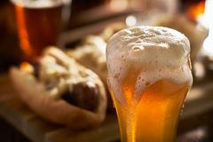 A fraîchement versé la bière ambre dans la tasse servie avec des bratwursts image libre de droits