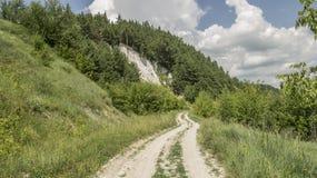 Fra la collina ed il fiume passa la strada fotografia stock