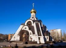 ` Fra le case, la città di kupina di Neopalimay del ` del tempio di Sosnovy Bor Fotografie Stock