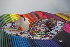 Fra le matite colorate calcoli la gallina bianca con il pettine e il pai rossi Fotografie Stock
