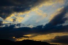 Fra le nuvole scure backlit dal tramonto c'è il pieno Immagine Stock