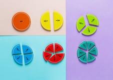 Fracciones coloridas de la matemáticas en los fondos brillantes de la violeta azul rosada matemáticas interesante para los niños  imagen de archivo