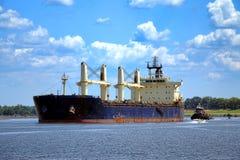 Fracht-Frachtschiff und Schlepper, die auf Fluss navigieren Stockfotografie