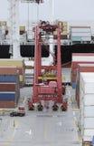 Frachtbehälter-LKW und ein Kran in einem Frachthafenterminal Stockfotos