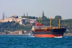Frachter mit Topkapi Palast im Hintergrund lizenzfreies stockbild