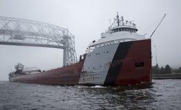 Frachterschiff, das unter Lufthubbrücke überschreitet Stockbilder