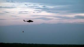 Frachtfeuerhubschrauber mit verschobenem Abflusskanalschöpflöffel fliegt vom Reservoir