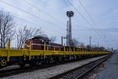 Frachtowy ładunku pociąg - żółty czarny Nowy 4 axled płaskich samochodów furgonu Pisać na maszynie: Burgas Bułgaria, Styczeń - 27 Obraz Royalty Free