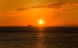 Frachtschiff auf dem Horizont bei Sonnenuntergang stockfotografie