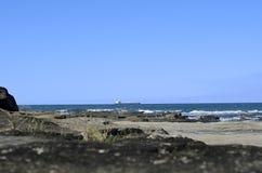 Frachtschiff nahe felsigen Ufern Stockfoto